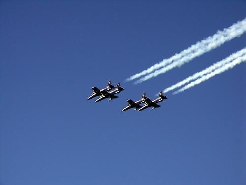 quattro aerei su cielo azzurro con scie