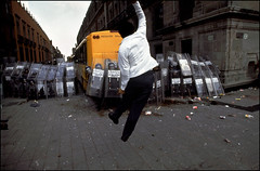 A protester jumps defiantly at riot police, Mexico City