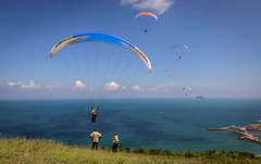 Men on Duty..! (photomaster.shifu) Tags: outings adventure paragliding photographer d300 kitlens photography starbursts sunrays sun jump mountain sea sky group blueskies 18140 taiwan taipei wanli specialshots specialmoments flying flyinghigh wind clouds ocean