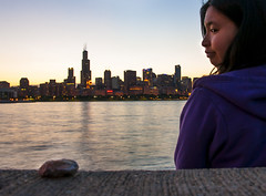 A rock and a hard place (Kevin Casey Fleming) Tags: chicago rock lake water metaphor girl beautiful grim sunset lights city building landscape portrait stone idea thinking hard place backlit story pretty person nikon d90 interesting thoughtful funny woman environment expression explore reflection young usa imagination illinois outdoors people photograph art face gaze lady meaningful vision