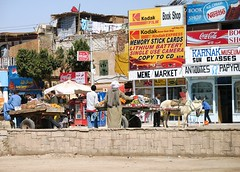 Karnak Mene Market (Firery Broome) Tags: egypt karnak menemarket market square busyintersection signs brightcolors red yellow orange blue white brown architecture donkey food produce fresh farmfresh police street streetscene dusty sand wagons rustic travel worldtravel 2006 canon powershota620 photoshop viveza alienskin exposurex2 egypt2006 landscape cityscape 365 africa