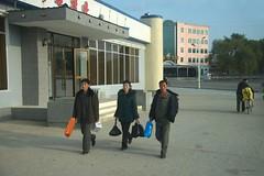 On the way (Frühtau) Tags: street city people woman man building fashion shop by shopping asian design asia leute walk strasse north scene korea east clothes korean stadt mann frau rajin causual koreanisch dprk szene passers nordkorea