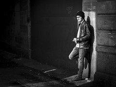 A Sliver Of Light (Leanne Boulton) Tags: monochrome urban street candid portrait portraiture streetphotography candidstreetphotography candidportrait streetlife man male face facial expression posture standing leaning mobile phone beanie hat sliver composition framing alley alleyway graffiti grime grit sunlight reflected tone texture detail depth natural outdoor light shade shadow shadows shadowplay city scene human life living humanity people society culture canon 7d 50mm black white blackwhite bw mono blackandwhite glasgow scotland uk