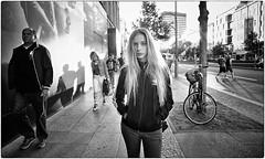 She Rocks (Steve Lundqvist) Tags: black white blackandwhite bw open street streetphotography sidewalk monochrome girl beauty womenswear sweatshirt adidas nikon nikkor 24mm sunset light strada road alley berlino berlin deutschland germany germania