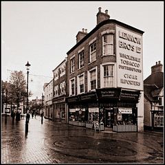 Market Place, Rugby (Jason 87030) Tags: shops trade marketplace wet rain weather warks warwickshire town former past history mono frame square tobacconist shoe key cutter cutting sign old building architecture shoppe uk england november 2016 thatsshoebusiness business lamp street