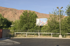 Moab, Utah (GC_Dean) Tags: moab utah moonset moon parkinglot fence sign mountain tree trees morninglight sky lamppost curb wall handpaintedsign shadows flora street emptiness mundane city cityscape urban urbanlandscape sociallandscape space colors color colours structure 7052