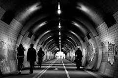 time tunnel (Wackelaugen) Tags: tunnel people street silhouettes circles vanishingpoint tbingen germany europe canon eos photo photography wackelaugen googlies black white bw blackwhite blackandwhite mono lines structure