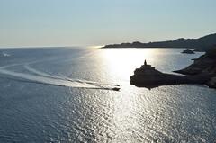 rientri (Il cantore) Tags: blue sea sky sun lighthouse water faro boats mediterranean mediterraneo wake mare gulf corsica barche cielo backlit sole acqua azzurro controluce golfo scogliera scia 15challengeswinner cligg