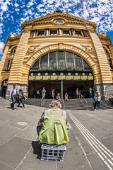 The Big Issue Man (Howard Ferrier) Tags: oceania sitting streetvendor flindersstreetstation crate transportbuildings walking standing clock actions clouds facade trainstation male vest steps melbourne cbd australia victoria architecture greatermelbourne clothing people centralbusinessdistrict railwaystation sit stand walk