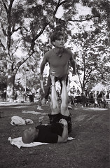 Up in the Air (salsadan101) Tags: film kodak tmax 400 35mm bw monochromatic street photography newyork ithaca city outdoors candid washington square performer gymnast person