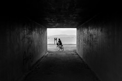 Rolling out of the tunnel (F719D) Tags: street streetphotography urban underground tunnel blackandwhite bw black white bike bicycle woman beach island sea seaside galicia