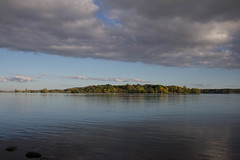 Lonely Island (lacygentlywaftingcurtains) Tags: island stones stlawrenceseaway water river sea ocean lake trees rocks shore sky clouds landscape nature outdoor outside iroquois morrisburg