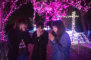 Young girls blowing on hands to warm in Christmas lights