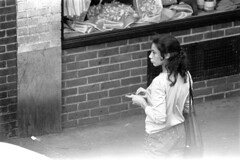 072868 04 (ndpa / s. lundeen, archivist) Tags: nick dewolf nickdewolf photographbynickdewolf blackwhite bw 1968 1960s 35mm july charlesstreet beaconhill candid people youngpeople pedestrians sidewalk boston massachusetts ma city citylife streetlife sliceoflife film monochrome blackandwhite building storefront clothes clothing fashion woman youngwoman longhair brunette purse handbag storewindow
