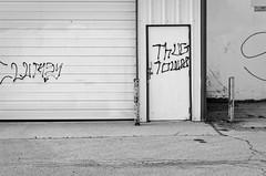 thug town (fallsroad) Tags: tulsaoklahoma graffiti industrial door decay bw blackandwhite nikond7000