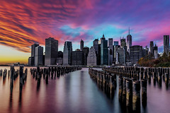 Sunset over Lower Manhattan - New York City (Insite Image) Tags: brooklynbridgepark city cityscape clouds leadinglines longexposure manhattan newyork newyorkny skyline skyscrapers sunset water pilings insiteimage