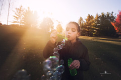(Rebecca812) Tags: trees sunset portrait sunlight girl grass childhood canon freedom child play candid joy happiness bubbles wideangle blow flare playful carefree rebecca812