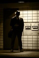 Mr X (Mona_Oslo) Tags: male hat underground light waiting monochrome shadow oslo monajohansson