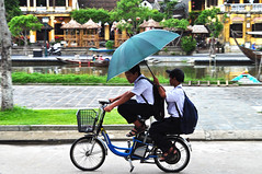 Co-operation (Roving I) Tags: electricscooters schoolboys umbrellas weather rain friends cooperation transport rivers uniforms backpacks hoian vietnam