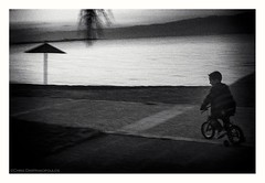 Dusk (s1nano) Tags: kamenavourla thalassa sea bicycle cyclist cycling child blackandwhite bw nikond60 nikkorafs35mm118gdx dark lowkey lowlight dusk movement motion skancheli