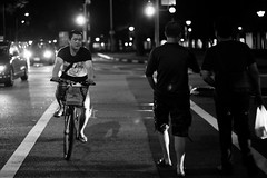 Just walk on by (ah.b|ack) Tags: road street bw bicycle zeiss walking t 50mm singapore crossing traffic sony riding wideopen f15 sonnar zm passby a7ii zeisscsonnart1550mmzm a7mk2