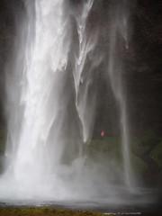 Waterproof (Feldore) Tags: iceland icelandic waterfalls red coat water figure waterproof feldore mchugh em1 olympus 1240mm dramatic pool seljalandsfoss