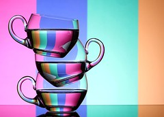 Rainbow Teacups (Karen_Chappell) Tags: tea teacup cup glass rainbow spectrum pink blue green orange colourful multicoloured refraction stilllife stack balance colours colour pastel