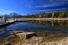 The filling station (alideniese) Tags: colterbaymarina jacksonlake grandtetonnationalpark wyoming usa landscape waterscape water lake reflection mountains marina boatramp sky clouds trees autumn fall nature colour color petrolbowser shoreline