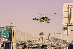 """""""Color of Autumn 2016 In NYC"""" (Helicopter Heading For Landing At Heliport NYC) (nrhodesphotos(the_eye_of_the_moment)) Tags: dsc0763072 theeyeofthemoment21gmailcom wwwflickrcomphotostheeyeofthemoment colorofautumn2016innyc autumn season helicopter flyingmachine bridge perspective sign brooklynbridge brooklyn skyline manhattan nyc streetlights metal glass buildings outdoor flag downtown heliport"""