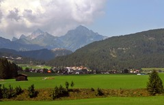 In Austria (Vee living life to the full) Tags: italy leger travel touring holiday nikond300 heathaze view road sky cloud blue water light evening sunset sunrays sunburst lowlight highlight people travelling sun mountain landscape rock towers austria