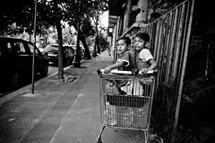 When You Don't Have a Stroller (stimpsonjake) Tags: nikoncoolpixa 185mm streetphotography bucharest romania city candid blackandwhite bw monochrome kids children faces family gypsy grocerycart stroller