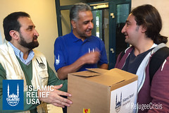 Islamic Relief USA CEO Anwar Khan hands a box to a refugee in Germany. Refugees came to the IR Germany office to shop for items they needed such as clothes.