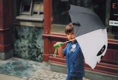 Hide (Amadeus Birca) Tags: street city summer girl smile rain umbrella panda child streetphotography