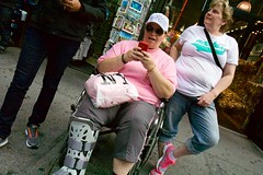 (heatherbirdtx) Tags: street newyork color hat bag phone availablelight candid wheelchair leg strangers tourists souvenir stolen brace purchase injured