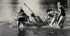 Launching of the SS  PMS (thepoocher7) Tags: outdoor monochrome blackandwhite river fun boatraces cardboardboat paddles push sove launching collegegirls splashing lifejackets oars sspms pms funny laughing shouting braidedhair shorts tshirts reflections water race watersports action running people candid portrait