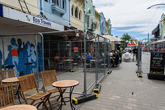 Still Unsafe Buildings (Jocey K) Tags: newzealand christchurch buildings city signs architecture people street sky newregentst cafes chairs tables clouds shops tramlines mural streetart painting artwork