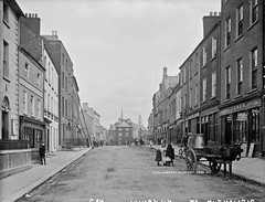 Parliament St. Kilkenny (National Library of Ireland on The Commons) Tags: robertfrench williamlawrence lawrencecollection lawrencephotographicstudio thelawrencephotographcollection glassnegative nationallibraryofireland parliamentstreet kilkenny ireland ladders painter children donkey cart milkchurns kilkennypeople irishpacket royalenfieldbicycles fallonco universitiesbill