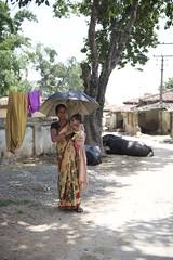 Portraits (The White Ribbon Alliance) Tags: mothers stare serious traditionalclothing rural woman females umbrella india wraindia wra portraits professionalphotographs whiteribbonalliance mom baby