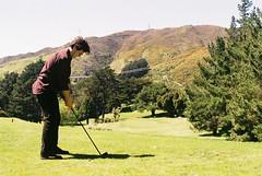 Teeing Up (Denzel De Ruysscher) Tags: 35mm pentax colour film explore drive golf green nature sky mountain sun