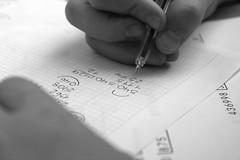 The tough stuff (isagsr) Tags: detail canon hands work homework blackandwhite 550d childhood pen paper maths learning life
