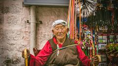 Tibet, candid shot of an old man sitting beside the street shop (Lhasa, China), 06-2016, 81 (Vlad Meytin, vladsm.com) (Vlad Meytin   Instagram: vmwelt) Tags: chengguan china khimporiumco meytin tibet tibetan vladmeytin art artgallery artists artphoto artworld asia candid carlzeiss chinese clothes fe5518 gallery highaltitude local man market oldman photography photographyart pictures sony sonya7 sonyalpha street streetphotography summer vladsm vladsmcom vmwelt wrinkles zeiss