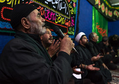 Iranian shiite muslim men listening to a mullah who preaches during muharram, Central county, Theran, Iran (Eric Lafforgue) Tags: 9people adultsonly ashura calligraphy ceremony colorimage commemorate commemoration faith groupofpeople horizontal hussain imamhussein indoors iran iranian iranianculture islam menonly middleeast mourning muharram muslim outdoors pain people persia pray praying religion ritual script selfflagellating selfflagellation shia shiism shiite tehran tradition trance worship worshiping theran centralcounty