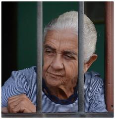Trinidad, Cuba (jkardysphotos) Tags: cuba trinidadcuba trinidad woman oldwoman window watching wrinkles lady windowbars snapseed streetphotography