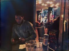 Caf Noir (Casey Hugelfink) Tags: munich mnchen coffeefellows kaffee caf espresso coffeebar cafeteria hauptbahnhof centralstation model mannequin street streetphotography coffee kaffeeschwarz noir movie man mafia beard people night city table window moviescene filmszene mobilephone cellphone handy