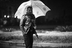 Rain Police (N A Y E E M) Tags: policeman umbrella rain monsoon portrait latenight hotel radissonblu maingate availablelight carwindow candid
