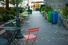 November Morning (stillsguy) Tags: nyc fall bryantpark morning dew tables folding chairs walkway leaf scatter light post colorful garbagepales cobblestone early bokeh bokehlicious vendor carts trees bushes lonely leica m9 50mm f14 summiluxm