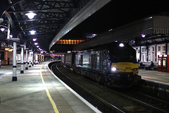 68020 Reliance - Stirling railway station (Andrew Edkins) Tags: class68 68020 relaince cat stormtrooper stirling nightshot railwayphotography scotland railwaystation dark lights october drs platform people uk intermodal boxes containers freighttrain geotagged canon photo image tesco diesel