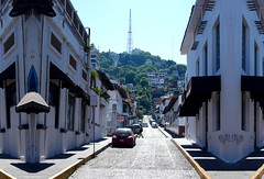 022POV (Symic) Tags: andrswilliamolsenrodriguez port vallarta mexico symmetry road reflect mirror street cobble hills green up ascend tower buildings cars line shop shopping