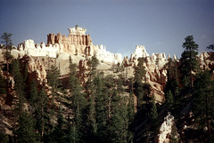 34-690 (ndpa / s. lundeen, archivist) Tags: nick dewolf nickdewolf color photographbynickdewolf 1970s 1973 film 35mm 34 reel34 utah southernutah southwesternunitedstates nationalpark brycecanyon brycecanyonnationalpark spires rock rocks rocky formation landscape terrain formations peaks outcropping outcroppings sky bluesky trees 1972