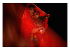 determination (handheld-films) Tags: family red portrait woman india blackbackground female togetherness child indian families young mother portraiture closeness motherhood society relationships protection isolated rajasthan protected subcontinent ruralindia